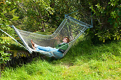 New Zealand, South Island: Woman in hammock at resort Lochmara Lodge near town of Picton on Marlborough Sounds. Photo copyright Lee Foster. Photo # newzealand125489