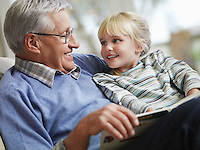 Grandfather reading to girl (3-4) close-up