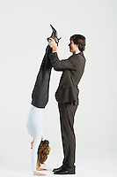 Young businessman holding legs of female colleague standing on hands profile