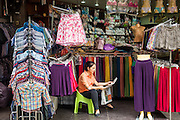 06 JUNE 2013 - BANGKOK, THAILAND:     A vendor reads her newspaper in her stall in Bobae Market in Bangkok. Bobae Market is a 30 year old market famous for fashion wholesale and is now very popular with exporters from around the world. Bobae Tower is next to the market and  advertises itself as having 1,300 stalls under one roof and claims to be the largest garment wholesale center in Thailand.       PHOTO BY JACK KURTZ
