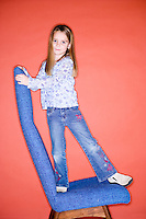 Model Released.seven year old female posing in front of orange background in blue jeans and with blue chair