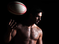 one caucasian sexy topless man portrait tossing a rugby ball on studio black background