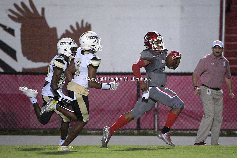 Edgewater quarterback Robert Harvey Jr., right, rushes for a long touchdown in front of Ocoee's Javon Cox, left, and Kendall Bohler (3) during the second half of a high school football game Monday, Oct. 9, 2017, in Orlando, Fla. Edgewater won 44-29. (Photo by Phelan M. Ebenhack)