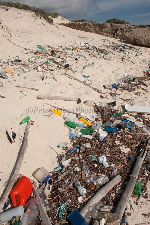 Beach trash washed up from ocean with Sand dunes in back.<br /> Playa Chiquitu<br /> Slagbaai National Park<br /> BONAIRE, Netherlands Antilles, Caribbean