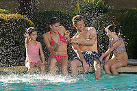 Family with two girls splashing, at edge of swimming pool