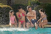 Family with two girls splashing, at edge of swimming pool