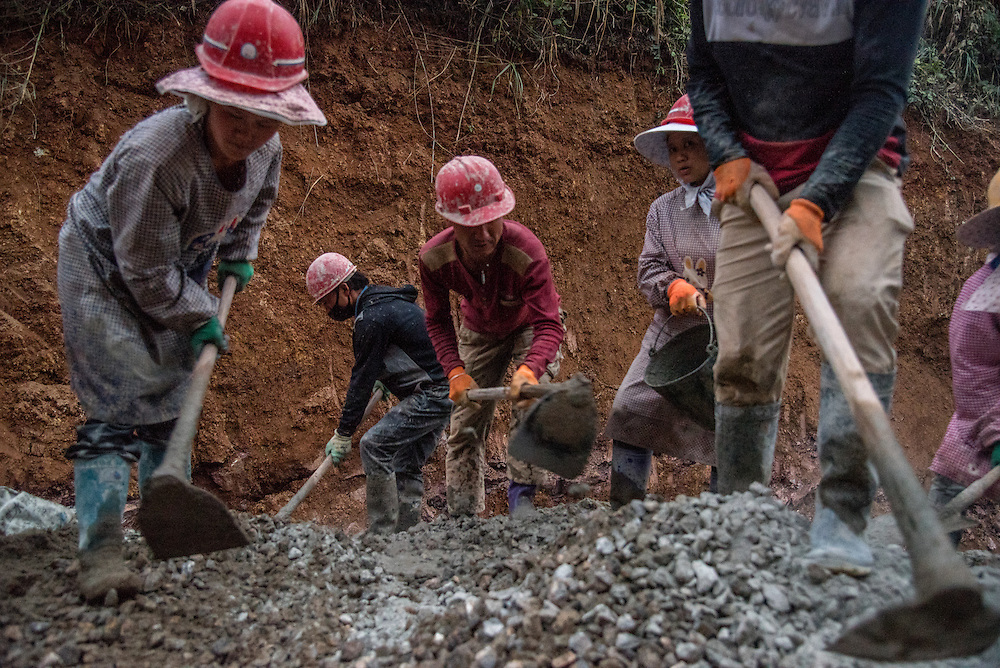 Construction workers use sand dredged from the Lancang (Mekong) river to make concrete, which will be used to build a new road near Simaogangzhen, Yunan, China.