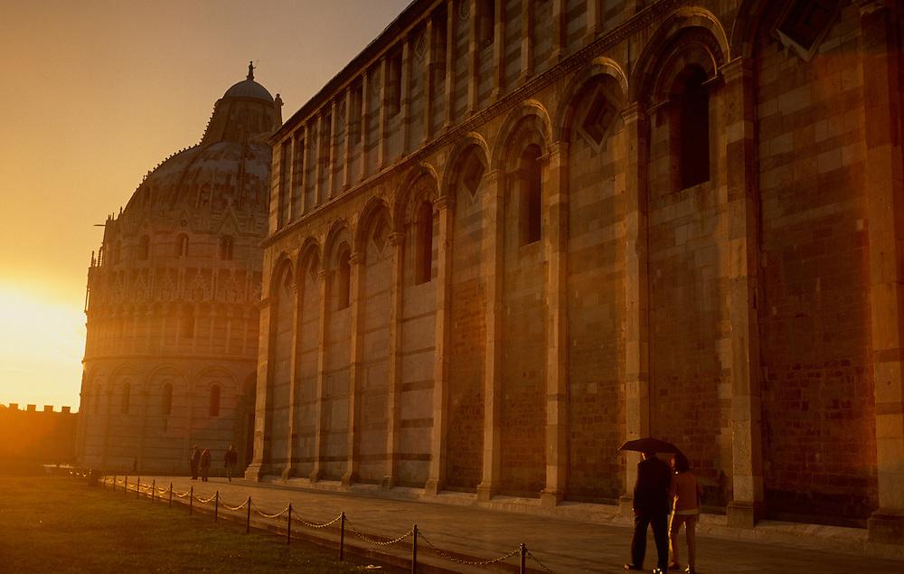 A couple walks by Campo dei Miracoli in Pisa