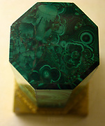 Malachite.  A carved and polished octagonal column with a brass base.