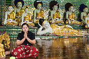 15 JUNE 2013 - YANGON, MYANMAR: A woman prays at Shwedagon Pagoda. The Shwedagon Pagoda is officially known as Shwedagon Zedi Daw and is also called the Great Dagon Pagoda or the Golden Pagoda. It is a 99 metres (325ft) tall pagoda and stupa located in Yangon, Burma. The pagoda lies to the west of on Singuttara Hill, and dominates the skyline of the city. It is the most sacred Buddhist pagoda in Myanmar and contains relics of the past four Buddhas enshrined: the staff of Kakusandha, the water filter of Koṇāgamana, a piece of the robe of Kassapa and eight strands of hair fromGautama, the historical Buddha. The pagoda was built between the 6th and 10th centuries by the Mon people, who used to dominate the area around what is now Yangon (Rangoon). The pagoda has been renovated numerous times through the centuries. Millions of Burmese and tens of thousands of tourists visit the pagoda every year, which is the most visited site in Yangon.  PHOTO BY JACK KURTZ