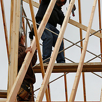 Thomas Wells | BUY AT PHOTOS.DJOURNAL.COM<br /> Tommy Harrison, left, and Adam Lesley of Don Wallace Construction install the roof truss as they build a new home in Fairpark in Tupelo on Wednesday.