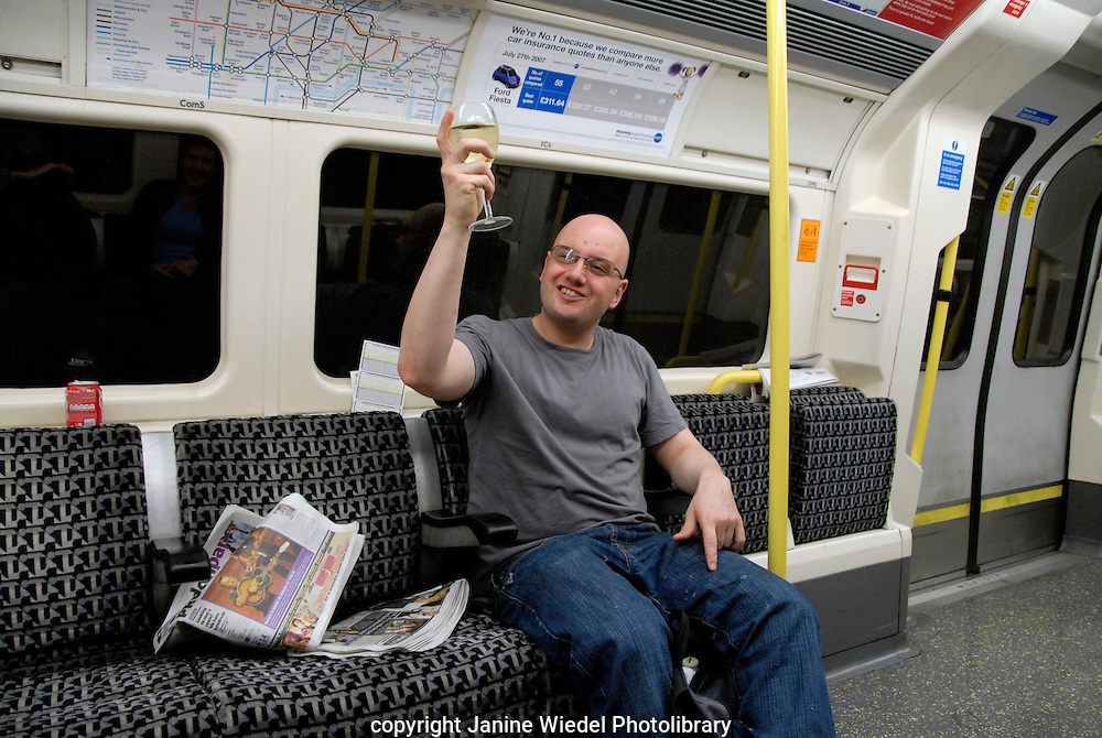 Waiter in way home drinking glass of wine on tube train.train