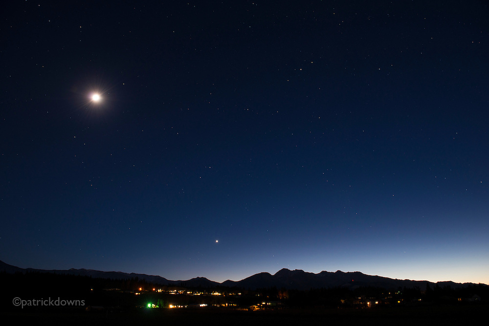 Looking south at the Olympic Range and homes nestled underneath the moon and Venus.