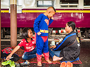 "03 JANUARY 2017 - BANGKOK, THAILAND: A family waits to board a train at Hua Lamphong Train Station in Bangkok. They were going back to their home province after visiting relatives in Bangkok over New Year's. Travelers flocked to Bangkok's  bus and train stations Tuesday, the last day of the long New Year's weekend in Thailand. The New Year holiday in Thailand is called the ""seven deadly days"" because of the number of fatal highway and traffic accidents. As of Monday Jan 2, 367 people died in highway accidents over the New Year holiday in Thailand, a 25.7% increase over the same period in 2016.        PHOTO BY JACK KURTZ"