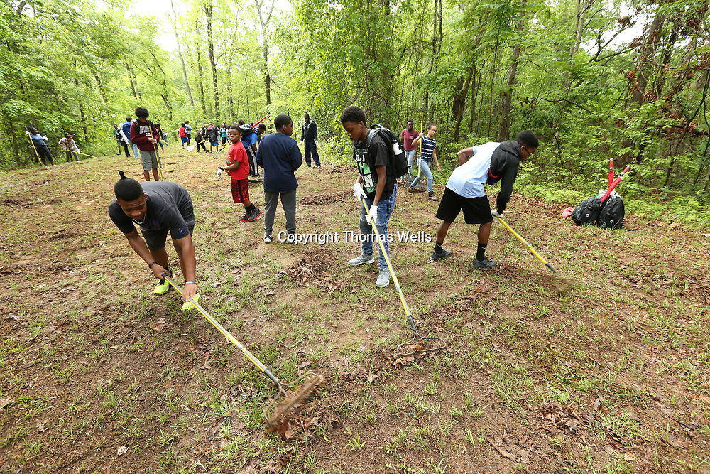 Cam Rucker, 14, from left, Olando Gates, 13, and Fred Hamer, 14, help clear a patch of land for new seeds at Tombigbee State Part as part of the Toyota's Adevnture Campout for youth from the Boys and Girls Club of North Mississippi
