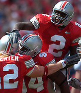 MORNING JOURNAL/DAVID RICHARD<br />Ohio State linebacker Bobby Carpenter, left, is congratulated by teammates Ben Huddle, center, and Ryne Robinson after his sack of quarterback Josh Betts of Miami yesterday in the first quarter.