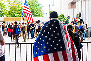 A counter-protester wears the American flag at the Freedom Rally at Westlake Park. Seattle, WA. August 13, 2017.