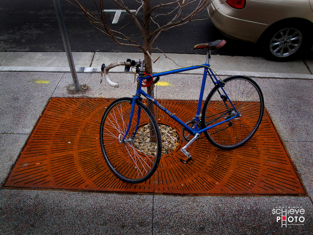 Blue bike on a rusty grate.