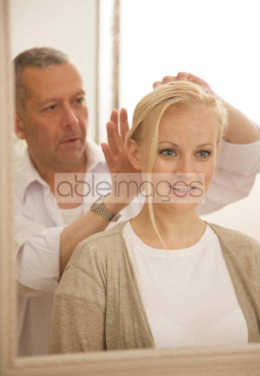 Close up of a hair stylist arranging woman hair