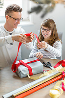 Happy father and daughter wrapping Christmas present at home