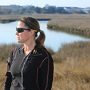 "Lisa Carter Hoffacker poses for a portrait at ""The Loop"" in Wrightsville Beach, N.C. Hoffacker, an avid runner is running the Quintiles Wrightsville Beach Half Marathon for the first time this year. Hoffacker has missed the Quintiles each year due to injury and even emergency gall bladder surgery. (Jason A. Frizzelle)"