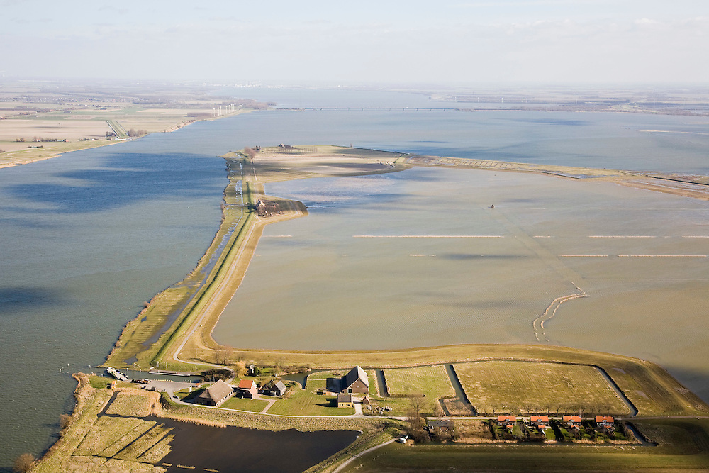 """Nederland, Zuid-Holland, Tiengemeten, 04-03-2008; eilandje in het Haringvliet, oorspronkelijk eigendom - binnen de dijken - van AMEV (Fortis Investments),en Natuurmonumenten (buitendijkse slikken); onder in beeld het buurtschap Tiengemeten, met haven voor de pont, links oude dijk (nu de functie van dam) naar overgebleven beorderijen; het eiland werd gebruikt voor de akkerbouw maar is inmiddels 'teruggegeven aan de natuur' (dijken deels doorgestoken) , de laatste boer is in 2006 vertrokken; huidig gebruik onder andere zorgboerderij en kan er gekampeerd worden; nieuwe natuur, onderdeel van de Ecologische Hoofdstructuur; natuurontwikkelingsgebied, natuurontwikkeling natuurontwikkeling; tiengemeenten; island in the Haringvliet, originally owned - within the dikes - by AMEV (Fortis Investments), and Natuurmonumenten (Society for conservation of nature); island was used for agriculture but has now """"been given back to nature""""; the last farmer left in 2006; current use, among other, care farms and camping; part of the National Ecological Network;  bottom of the image the hamlet Tiengemeten, with port for the ferry, and on the left the old dike (now the function of dam) to remaining farms; the.nature area, nature nature; .    .luchtfoto (toeslag); aerial photo (additional fee required); .foto Siebe Swart / photo Siebe Swart"""