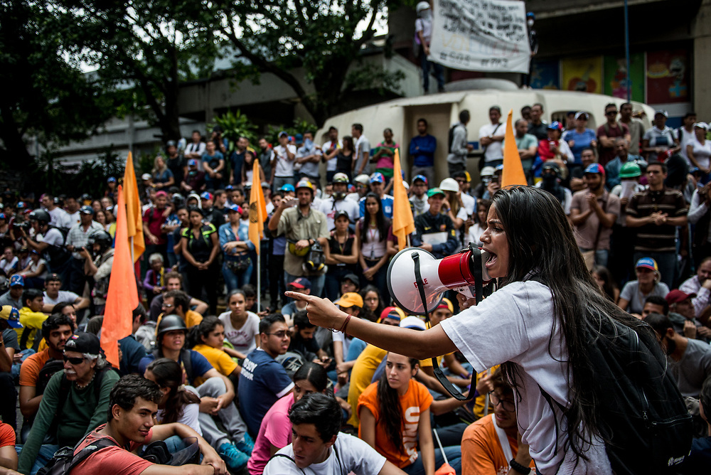 CARACAS, VENEZUELA - JUNE 2, 2017: University students participate in a sit-in as a form of peaceful, anti-government protest in Caracas. The streets of Caracas and other cities across Venezuela have been filled with tens of thousands of demonstrators for nearly 100 days of massive protests, held since April 1st. Protesters are enraged at the government for becoming an increasingly repressive, authoritarian regime that has delayed elections, used armed government loyalist to threaten dissidents, called for the Constitution to be re-written to favor them, jailed and tortured protesters and members of the political opposition, and whose corruption and failed economic policy has caused the current economic crisis that has led to widespread food and medicine shortages across the country.  Independent local media report nearly 100 people have been killed during protests and protest-related riots and looting.  The government currently only officially reports 75 deaths.  Over 2,000 people have been injured, and over 3,000 protesters have been detained by authorities.  PHOTO: Meridith Kohut