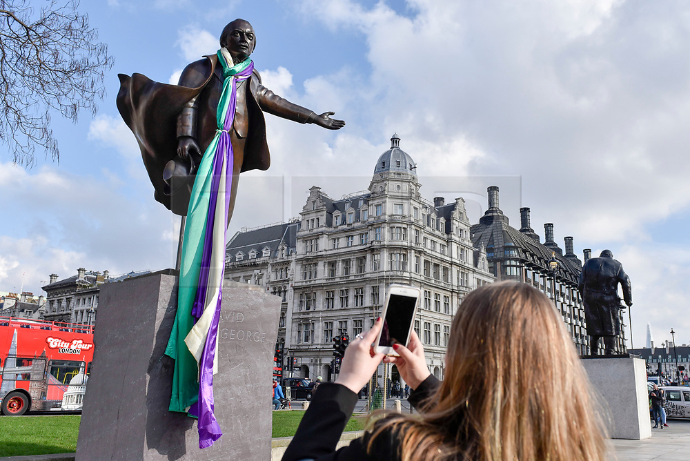 © Licensed to London News Pictures. 06/02/2018. LONDON, UK. A banner in the colours of the suffragette movement has been placed on the statue of David Lloyd George in Parliament Square.  It is 100 years since the Representation of the People Act was passed, granting some women over the 30 in the UK the right to vote for the first time but David Lloyd George was the Chancellor of the Exchequer who, at the time, opposed women getting the vote.  Photo credit: Stephen Chung/LNP