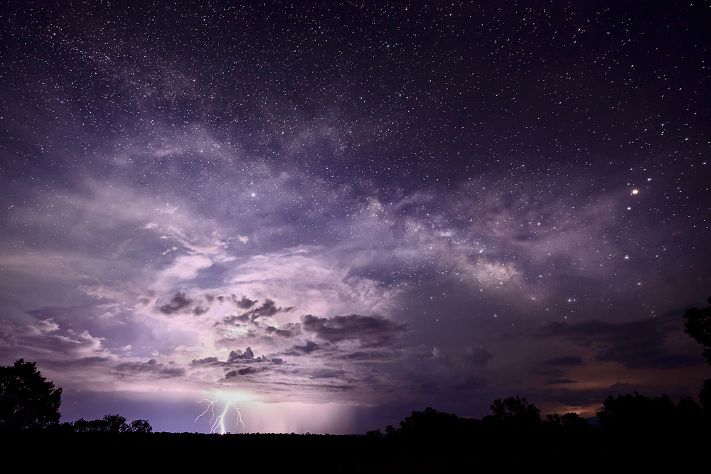 Lightning erupts from a thunderstorm, and the Milky Way graces the night sky above the Grand Canyon.