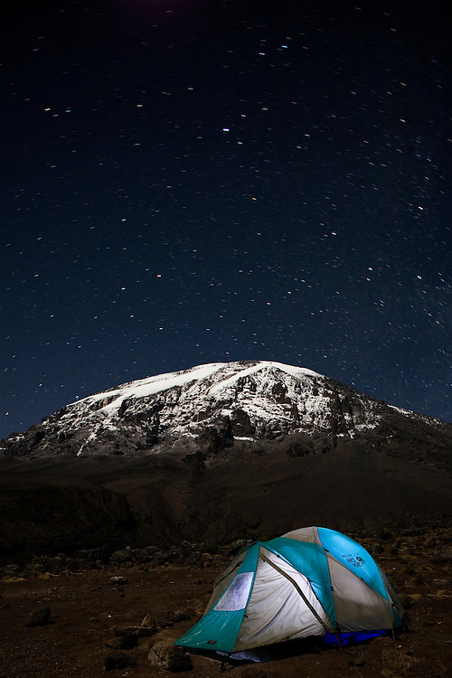 Africa, Tanzania, Kilimanjaro National Park, (MR) Climbing parties' tents glow against night sky at Karanga Camp (13000') during climbing expedition