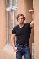 hot guy leaning against a rustic building