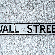 A sign for Wall Street against a white stucco wall in Beaumaris on the island of Anglesey of the north coast of Wales, UK.
