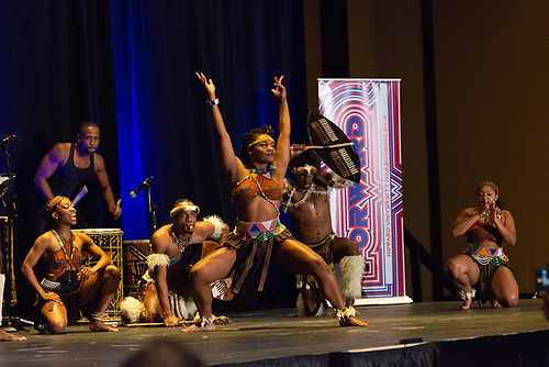 A group of Step Afrika! dancers in traditional clothing perform at the Annual Jazz Brunch as drummers play in the background.