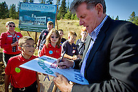 Logan Shults, a Classical Christian Academy Robotics Team member, takes a peek at Gov. Butch Otter's note on a welcome banner following the ground breaking ceremony Thursday for the Star Science Center near Rathdrum.
