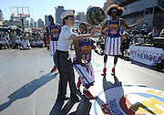 "The World Famous Harlem Globetrotters teach West Point Cadet Captain Julie Dillon, of Stafford Springs, CT., how to spin the ball during an exhibition game on the flight deck of the Intrepid Sea, Air & Space Museum, Monday, Oct. 6, 2014, in New York.  The Globetrotters played the exhibition game to announce the dates for their 2014-15 North American Tour, during which they will honor a ""Hometown Hero,"" a current or past member of the U.S. armed forces, at each stop on their tour.  (Photo by Diane Bondareff/Invision for the Harlem Globetrotters/AP Images)"