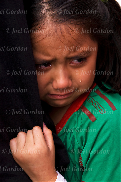 Something had happen during the Mexican Day parade in NYC, a young Mexican Hispanic girl afraid holds on to her father. She is fearful, scared or uneasy and is about to cry tears.
