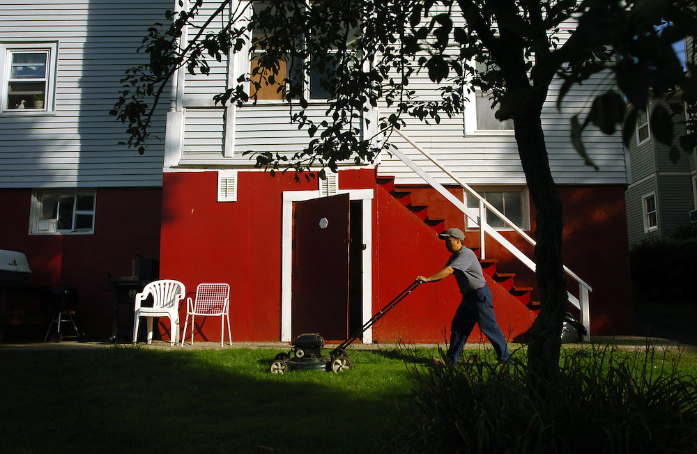 Steel worker Bonifacio Soto mows his lawn for the final time in 2006 on his Wallingford, Connecticut property. Soto sold this three-family home and in turn purchased a one-family home in town. Soto also owns a home back in Mexico.