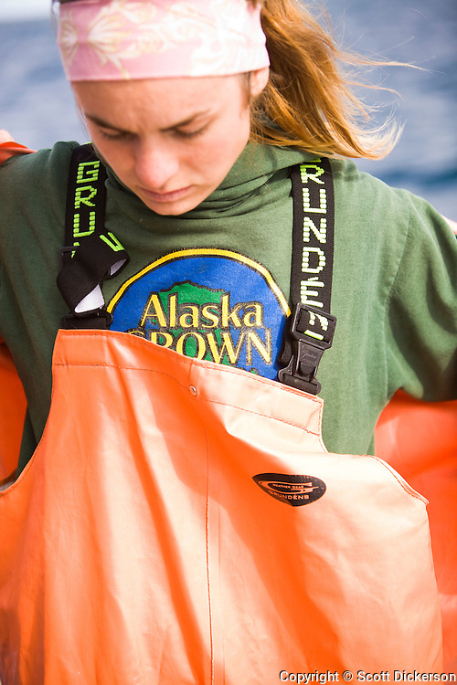 Claire Laukitis puts on raingear over her 'Alaska Grown' sweater while commercial sockeye salmon fishing in the Eastern Aleutian Islands, area M, region aboard the F/V Lucky Dove.