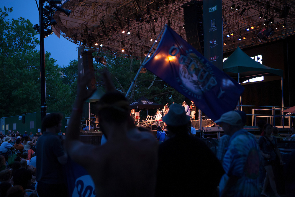 Spectators from Occupy Wall Street wave an Occupy banner during the concert. Guthrie is a supporter of the movement.