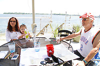 Alex Schibli with his wife Noelva Vigoya visit his island - Rat Island for a picnic on June 15, 2012 ..The little girl is Gabrielle Esposito - their grandchild. .In this shot they are sitting on the deck of his house in The Bronx and Rat Island is the small piece of land visible in the in the distance.