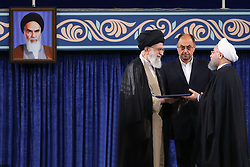 Handout photo - Iranian supreme leader Ayatollah Ali Khamenei (L) gives his official seal of approval during the swearing in ceremony of President Hassan Rouhani (R) to serve his second term, in Tehran, Iran, on August 3, 2017. Photo via Parspix/ABACAPRESS.COM