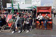 Young Germans enjoy spring sunshine on deckchairs and beach-style seating, in Alexanderplatz, Berlin Mitte.