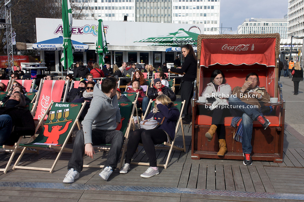 Young Germans enjoy spring sunshine on deckchairs and beach-style seating, in Alexanderplatz, Berlin Mitte.