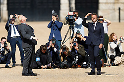 © Licensed to London News Pictures. 18/06/2020. London, UK. President Macron (R) and Prime Minister Boris Johnson watch from Horse Guards Parade as a fly past by the Royal Air Force (RAF) Red Arrows and the Patrouille de France (PAF), the aerobatics demonstration team of the French Air Force takes place over central London. Today's events commemorate the 80th anniversary of the Second World War resistance leader General Charles de Gaulle's historic broadcast to occupied France on June 18, 1940. Photo credit: Peter Macdiarmid/LNP