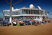 Passengers enjoying the sun on the upper deck onboard the cruise ship Oasis of the Seas. The ship, currently the largest in the world, is owned by Royal Carribean Cruise Line.