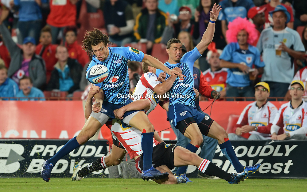JOHANNESBURG, South Africa, 14 April 2012. Zane Kirchner of the Bulls is tackled by Deon van Rensburg of the Lions while Bjorn Basson of the Bulls is tackled without the ball by Andries Coetzee of the Lions during the Super15 Rugby match between the Lions and the Bulls at Coca-Cola Park in Johannesburg, South Africa on 14 April 2012. The Bulls won this away game 32-18.<br /> Photographer : Anton de Villiers / SASPA