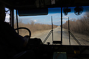 A school bus driver navigates a muddy unpaved road in Solon, Iowa on Tuesday, March 8, 2016.