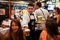 """Opened in 1956, Jobi bar and restaurant is a beloved local favorite where Cariocas (residents of Rio de Janeiro) drink glasses of """"choppe"""", beer, in the posh neighborhood of Leblon, in Rio de Janeiro, Brazil, on Friday, Feb. 1, 2013."""