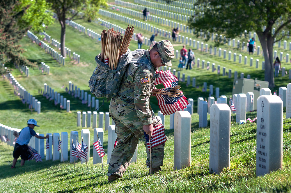 em052617a/a/Orlando Romero, from Espanola and with the U.S. Army Reserves, along with his son C.J. Romero, 5, left, plant flags on graves at the Santa Fe National Cemetery on Friday May 26, 2017. The flags on the over 58,000 graves at the cemetery will be there for the Memorial Day weekend as well as events on Monday. (Eddie Moore/Albuquerque Journal