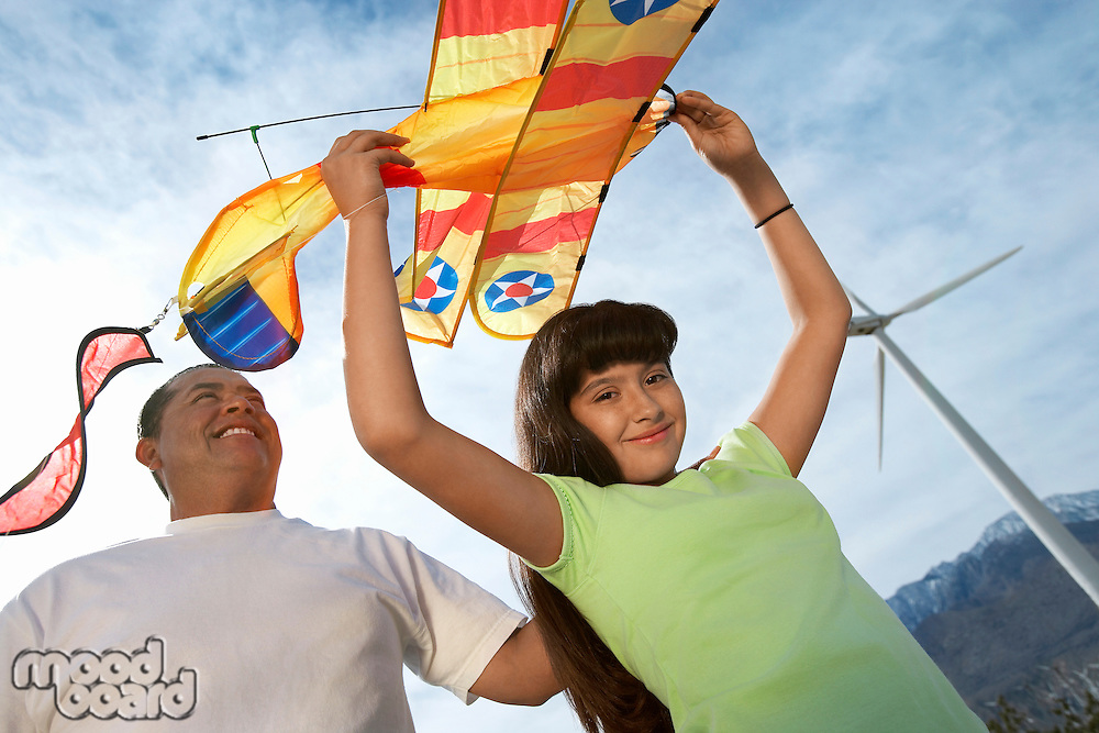 Girl (7-9) holding airplane kite with father at wind farm